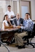 7159234-happy-office-workers-meeting-at-table-in-boardroom-working-together[1]